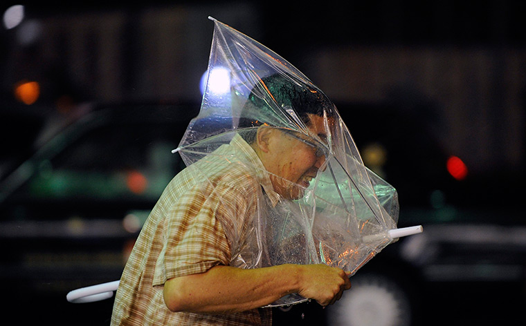 A man struggles to control his umbrella against strong winds in Tokyo